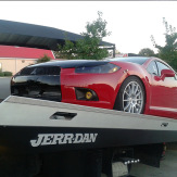 red sports car being towed